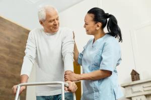 Caregiver woman helping the senior man